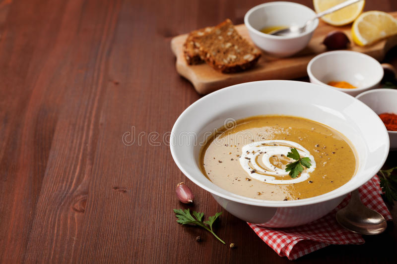 Lentil cream soup in a bowl with spices turmeric, paprika and garlic stock photography