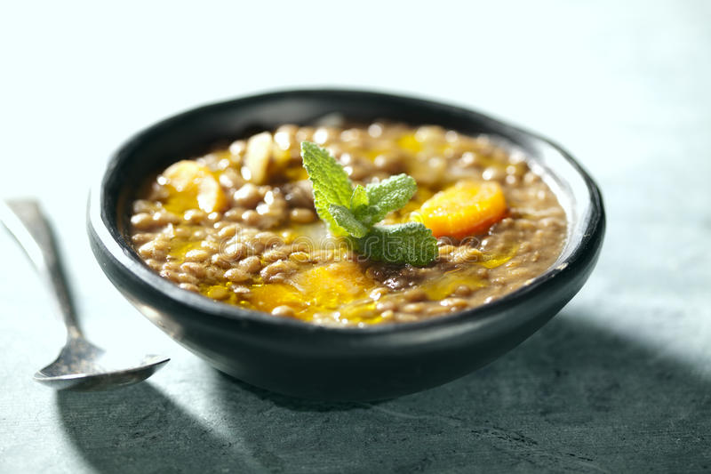 Lentil soup. Closeup of lentil soup, the lentils have cooked for 3 hours in order to form its own thick sauce, it also has carrots and onions royalty free stock photos