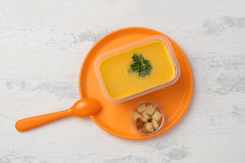 Lentil vegetable soup on a plastic plate. Lentil vegetable soup in a plastic box on a plastic colored plate with a plastic spoon. on a white wooden table royalty free stock photography