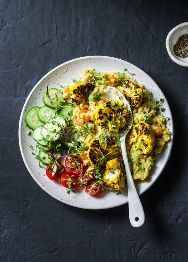 Lentilhas amarelas da ab?bora, couve-flor roasted da c?rcuma e vegetais em uma bacia - alimento do vegetariano em um fundo escuro imagens de stock royalty free