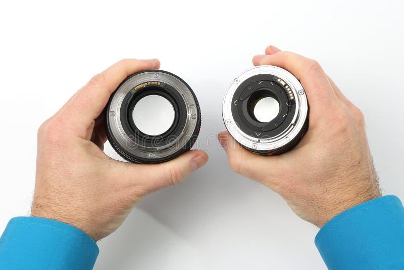 Lentille deux pour l'appareil-photo dans les mains sur le fond blanc images stock