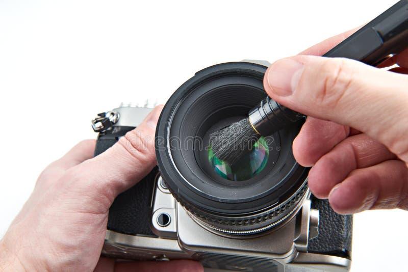 Lentille photographique de nettoyage de la poussière avec la brosse photos stock