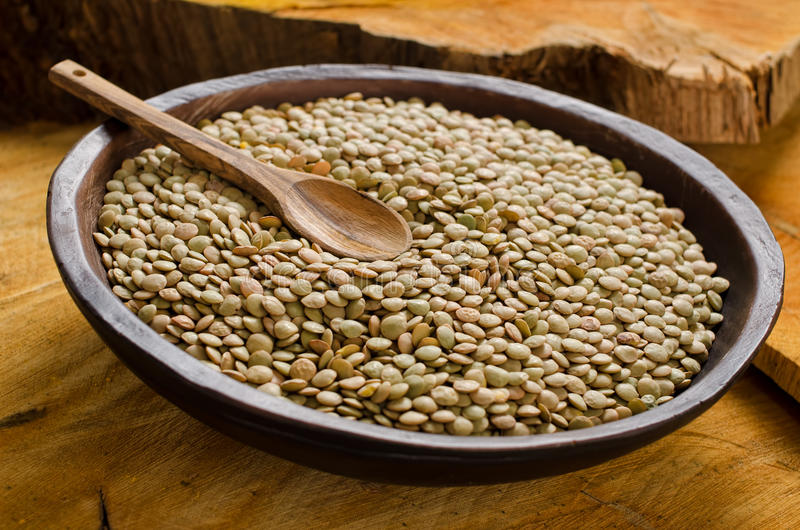 Lentils. A bowl of lentils with a wooden spoon in a rustic bowl against a rustic wooden background royalty free stock photo