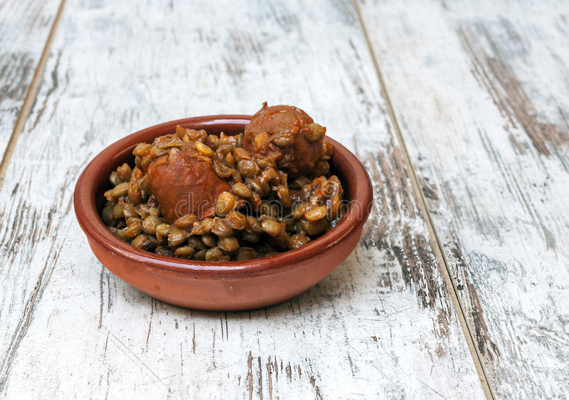 Lentils. With chorizo served in a clay plate surrounded by rustic background royalty free stock image