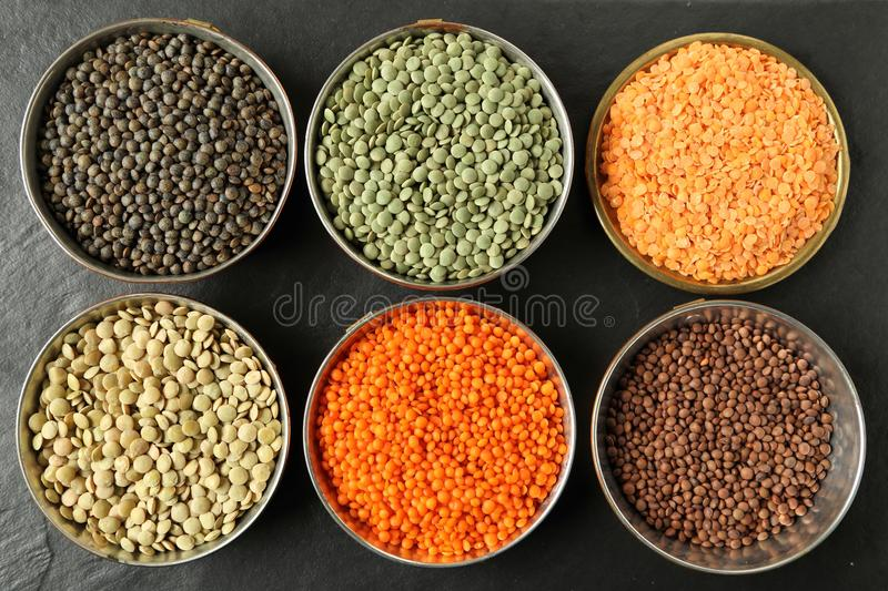 Lentils. Colorful lentils in metal bowls on a dark background stock photo