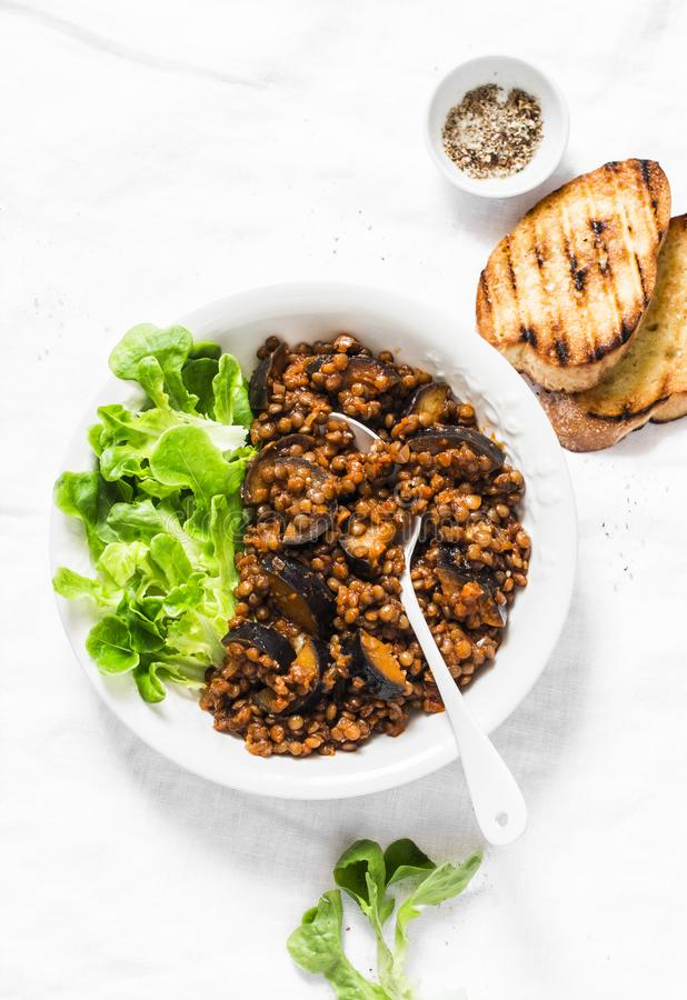 Lentils eggplant stewed in tomato sauce on light background, top view. royalty free stock image