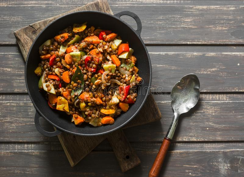 Lentils and seasonal garden vegetables braised in the pan on wooden background, top view. stock photo