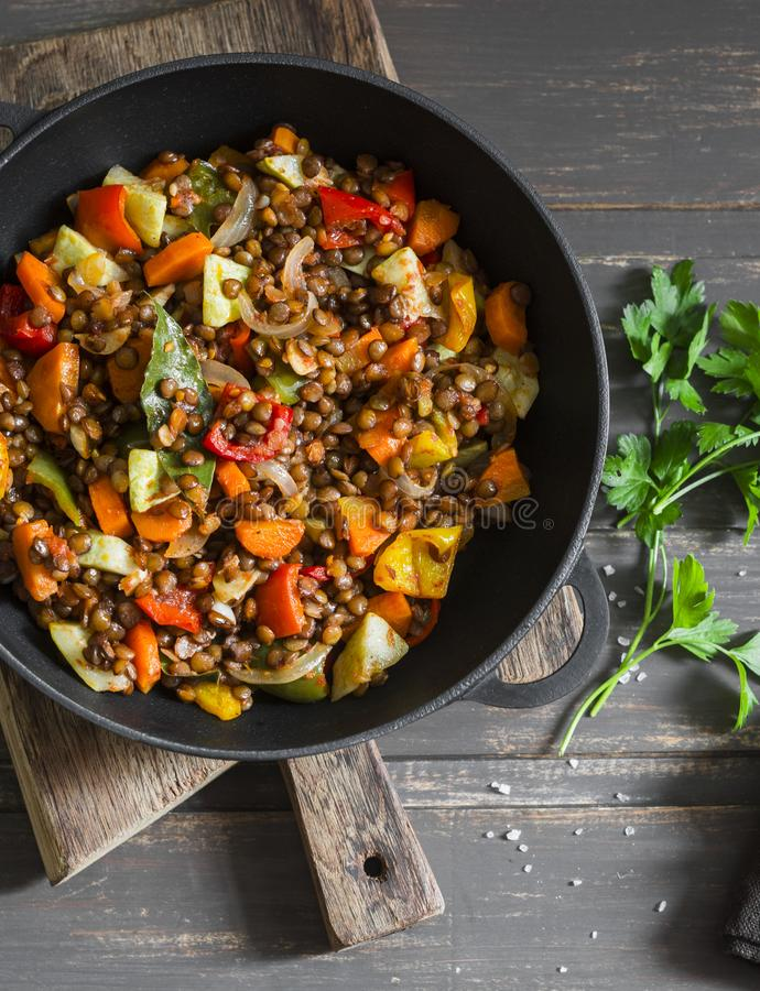 Lentils and seasonal garden vegetables braised in the pan on wooden background, top view royalty free stock photos
