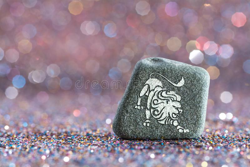 Leo zodiac sign. A green stone with Leo zodiac sign on glitter boke light background stock photography
