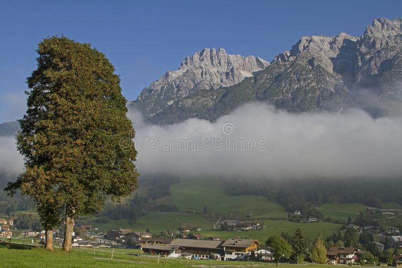 Leogang in front of the Loferer Steinberge. Under the cloud cover the popular tourist resort Leogang and above the mighty peaks of the Loferer mountains stock photo