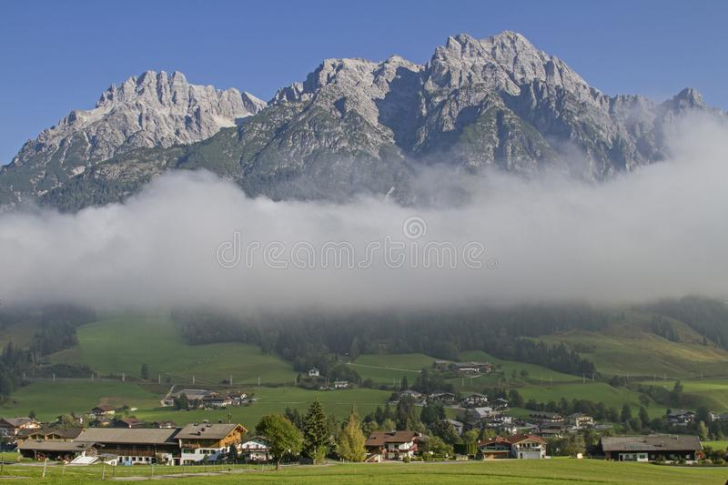 Leogang in front of the Loferer Steinberge. Under the cloud cover the popular tourist resort Leogang and above the mighty peaks of the Loferer mountains stock photos