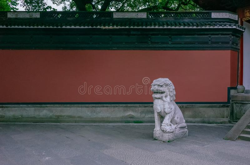 Leone di pietra e parete rossa vicino all'entrata di Yue Fei Temple, vicino al lago ad ovest, a Hangzhou, la Cina fotografia stock
