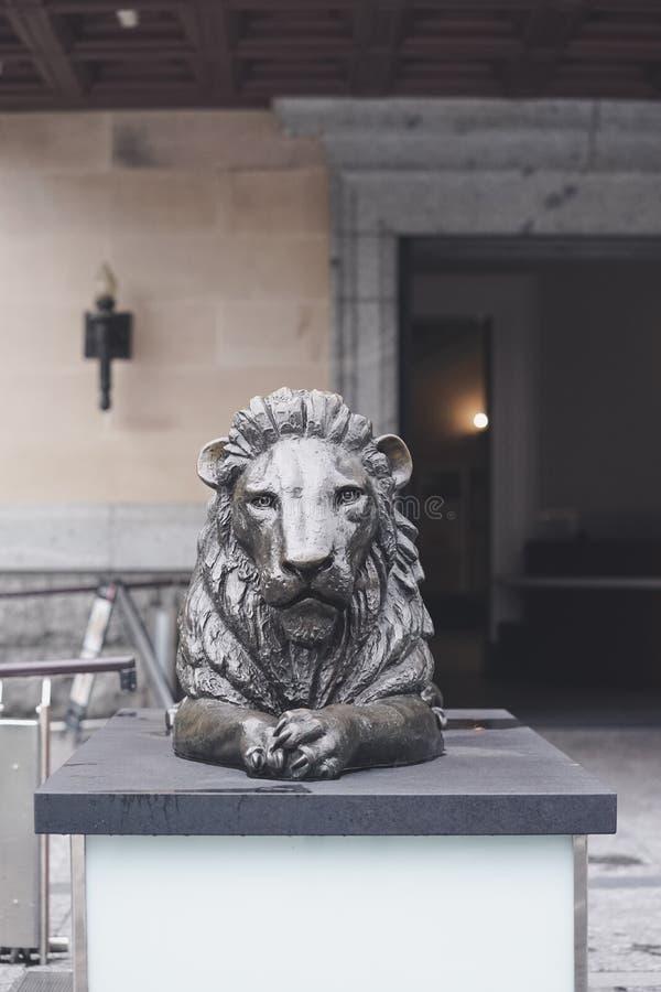 Leone scuro Una scultura del leone fatta da bronzo davanti ad un mus fotografia stock