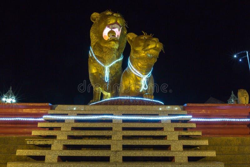 Leones de oro iluminados en la noche, centro de Sihanoukville Camb foto de archivo