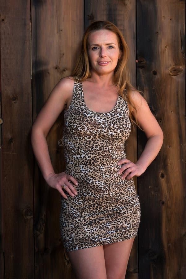 Leopard print dress. Beautiful tall redhead in a leopard print dress royalty free stock photography
