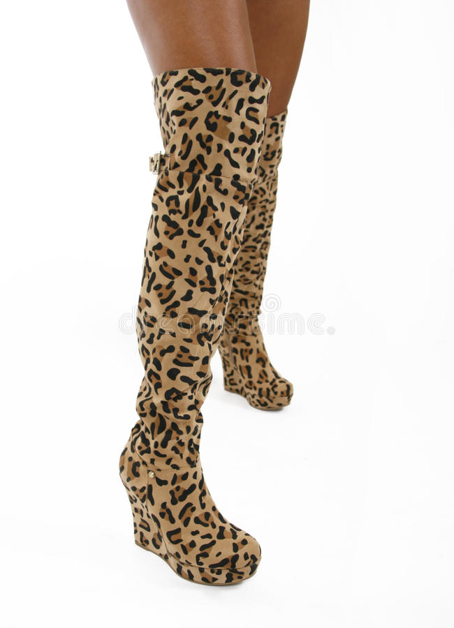 Leopard skin boots on legs stock photo