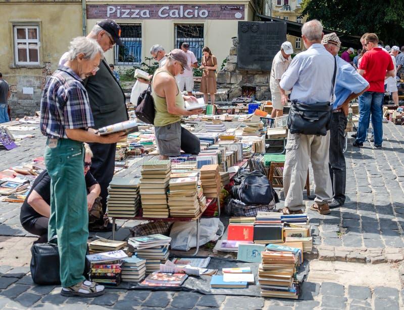 Leopoli, Ucraina - luglio 2015: Gli uomini e le donne scelgono e affare ed i venditori stanno vendendo i vecchi libri rari e gli  immagini stock