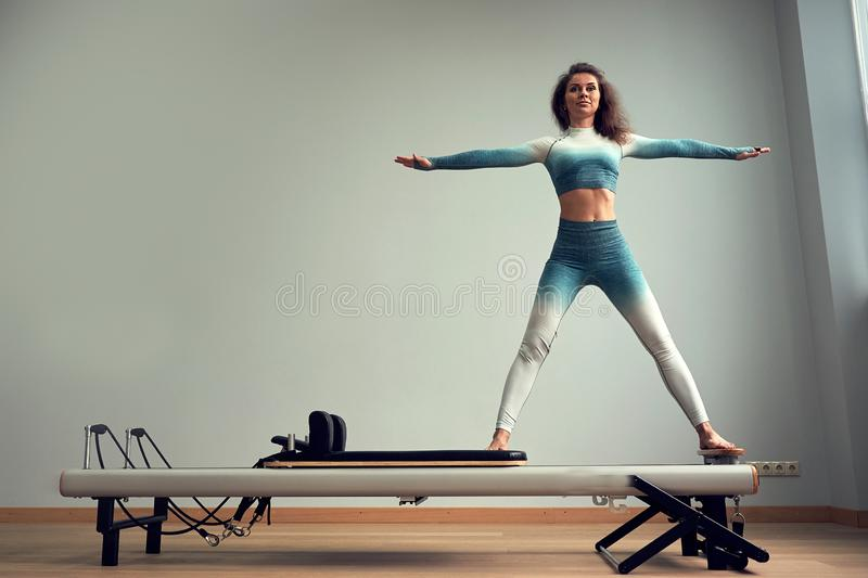 Leotard workout pilates training. athletic pilates reformer exercises. pilates machine equipment. young asian woman royalty free stock photography