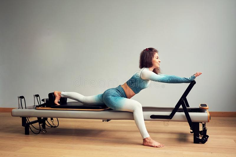 Leotard workout pilates training. athletic pilates reformer exercises. pilates machine equipment. young asian woman. Pilates stretching sport in reformer bed royalty free stock photos