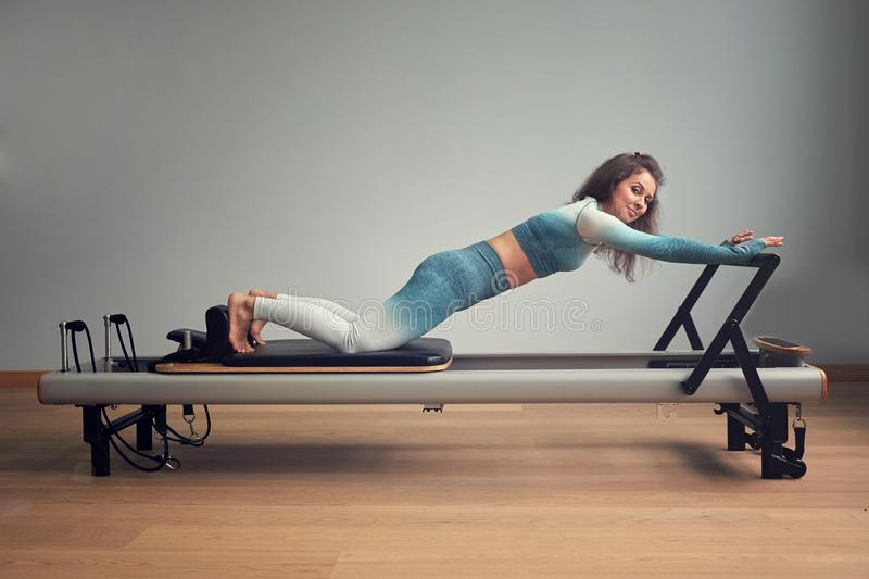 Leotard workout pilates training. athletic pilates reformer exercises. pilates machine equipment. young asian woman. Pilates stretching sport in reformer bed stock photography