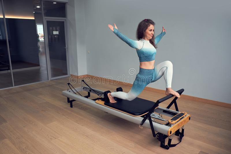 Leotard workout pilates training. athletic pilates reformer exercises. pilates machine equipment. young asian woman. Leotard workout pilates training. athletic royalty free stock photos