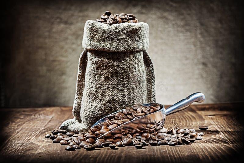 Lepel en zak met koffiebonen op uitstekende houten lijst stock fotografie