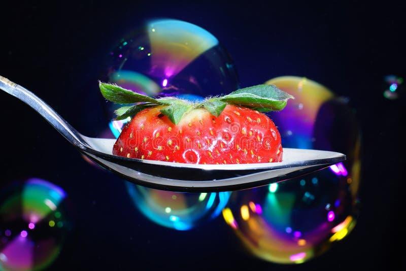 Lepel met een plak van rijpe aardbeien met peduncle, achtergrond met blauwe backlight stock fotografie
