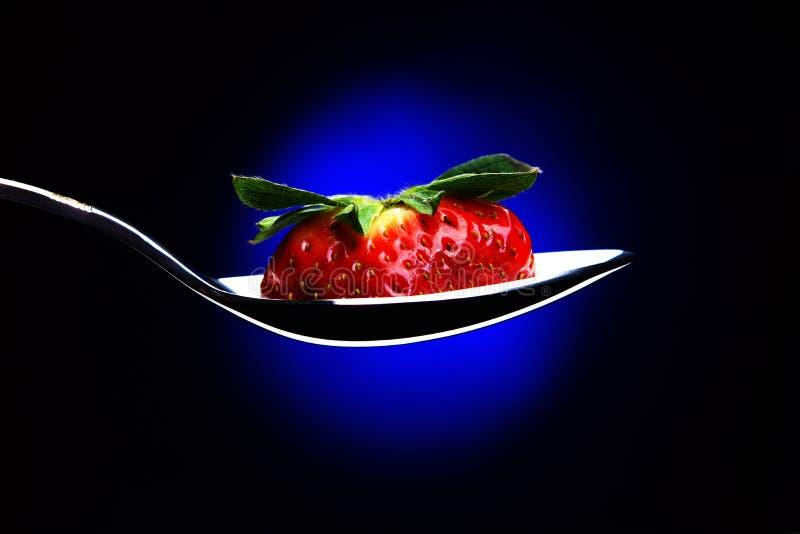 Lepel met een plak van rijpe aardbeien met peduncle, achtergrond met blauwe backlight, zeepbels royalty-vrije stock foto's