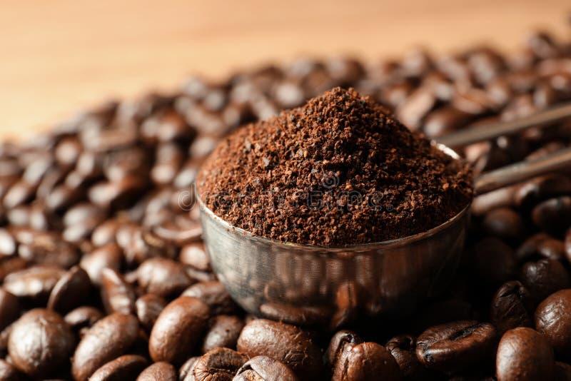 Lepel met koffiedik en geroosterde bonen op lijst royalty-vrije stock afbeelding