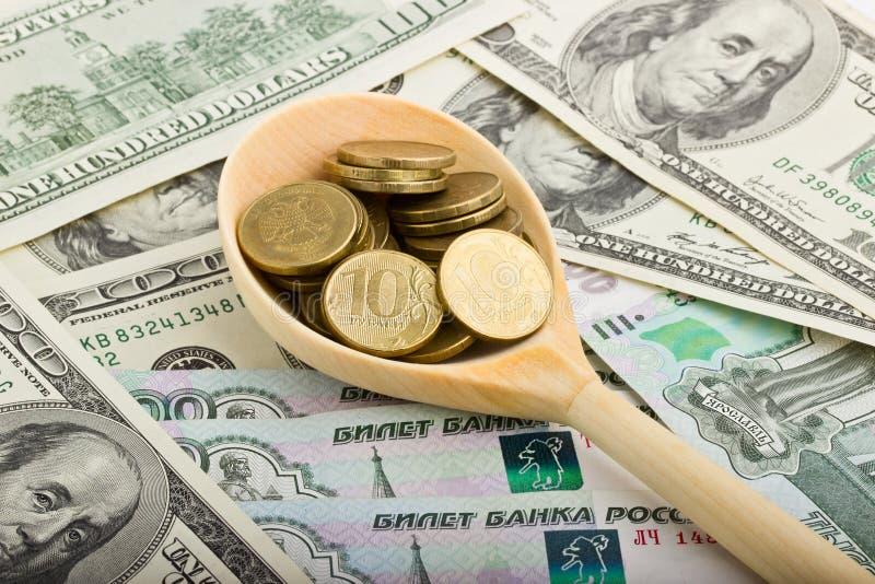 Lepel met muntstukken op een achtergrond van geld royalty-vrije stock afbeelding