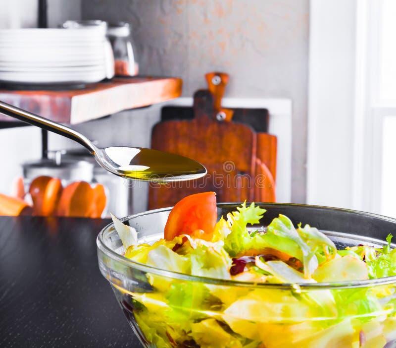Lepel met olijfolie op Italiaanse verse salade en tomaat op houten keuken royalty-vrije stock foto's