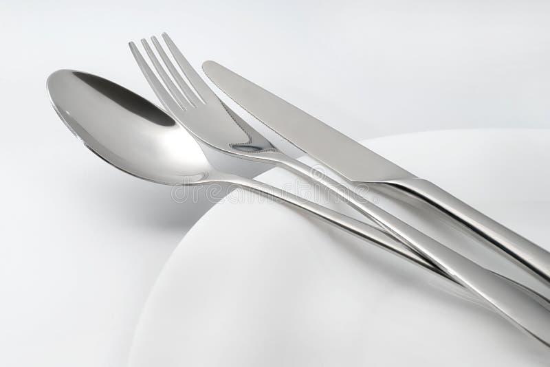 Lepel, vork en mes op witte lege plaat royalty-vrije stock afbeeldingen