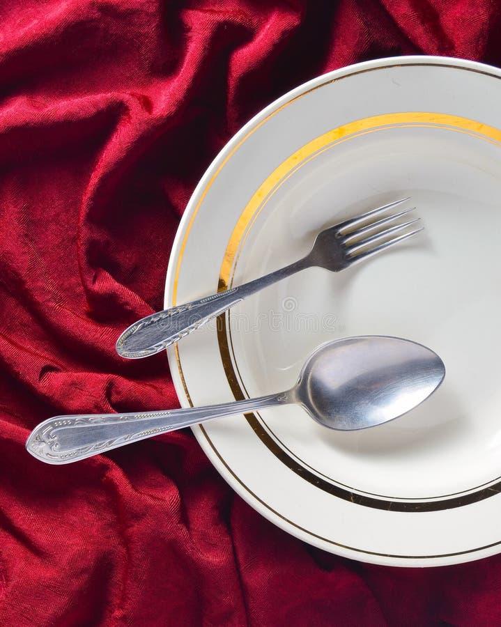 Lepel, vork, plaat op een rood zijdetafelkleed Romantisch diner Hoogste mening stock fotografie