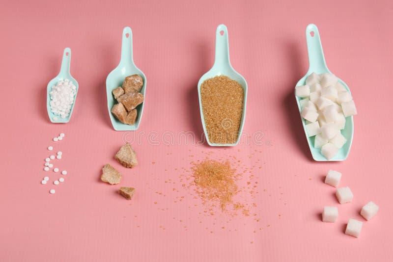 Lepels met verschillende soorten suiker en zoetmiddeltabletten op kleurenachtergrond royalty-vrije stock fotografie