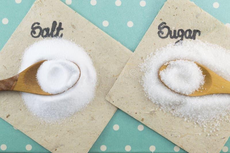 Lepelshoogtepunt van zout en suiker op een kleurrijke achtergrond royalty-vrije stock foto