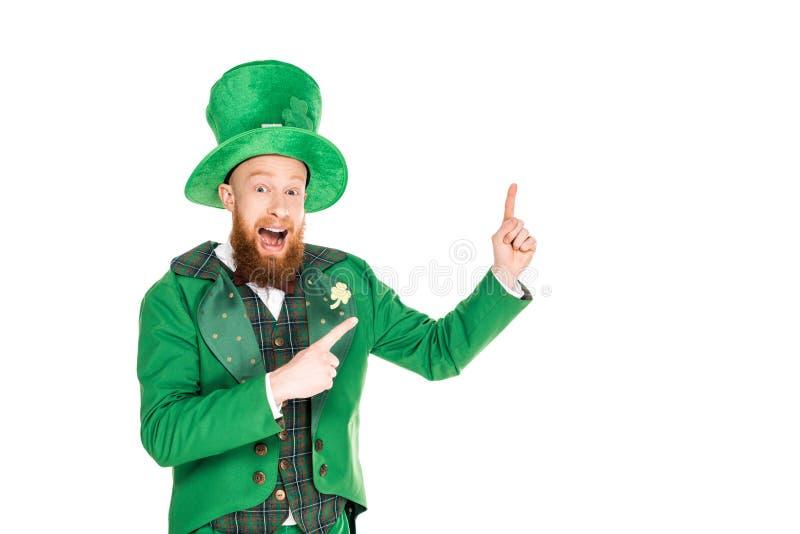 Leprechaun bello emozionante in vestito verde e cappello che presenta qualcosa fotografia stock