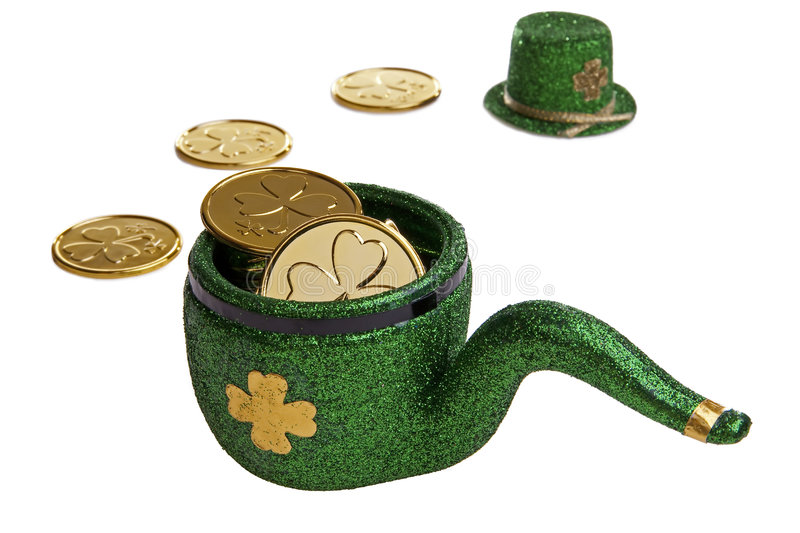 Leprechaun Pipe. Green Leprechaun's pipe filled with lucky shamrock coins and a green top hat in the background royalty free stock photo