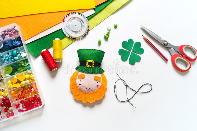 Leprechaun sewn from felt craft. St. Patrick`s Day. Leprechaun sewn from felt. St. Patrick`s Day. Rainbow beads in a box. Favorite hobby diy. Decor for the royalty free stock photos