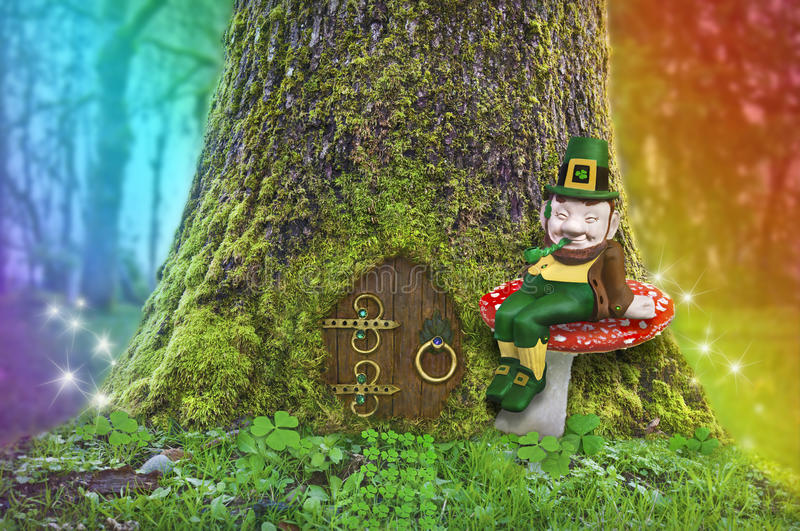 Leprechaun sitting on a mushroom in forest with rainbow and fairy lights royalty free stock photography
