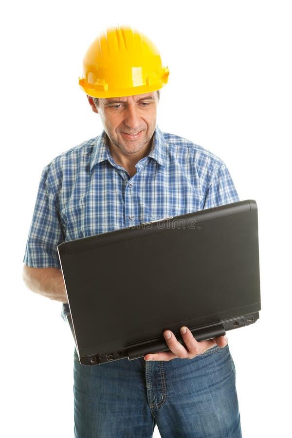 leptop för hård hatt genom att använda den slitage arbetaren arkivfoto