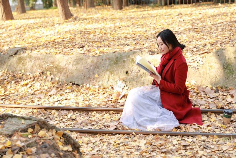 Ler dentro a natureza é meu passatempo, menina leu o livro senta-se nos trilhos completamente das folhas do biloba da nogueira-do foto de stock royalty free