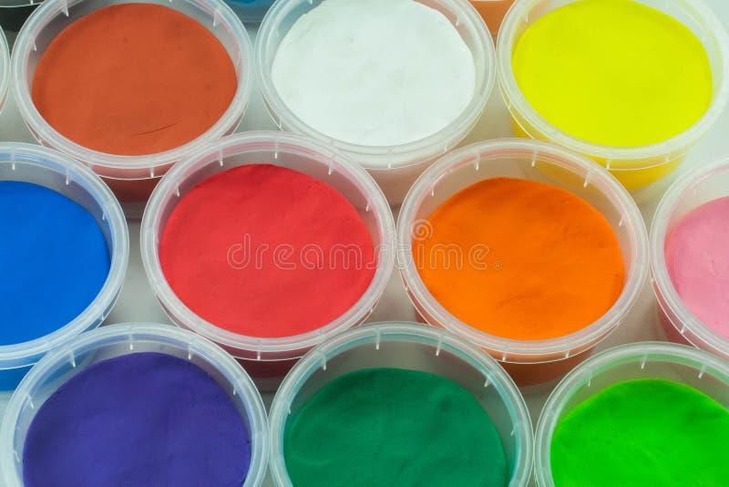 Lera eller plasticine i färgrik bakgrund för kopp royaltyfri foto