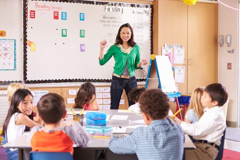Leraar bij de voorzijde van klasse met basisschooljonge geitjes royalty-vrije stock foto