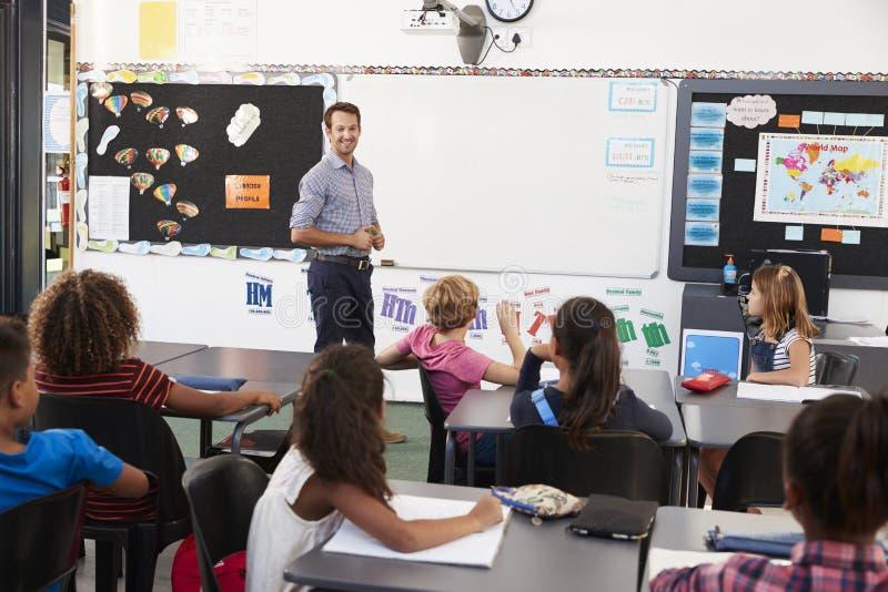 Leraar bij voorzijde van klasse in een basisschoolles stock foto's