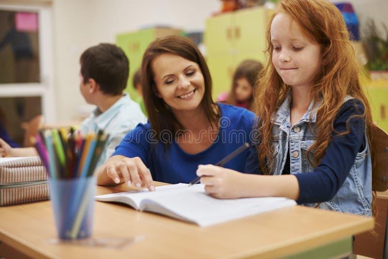 Leraar die aan haar leerling helpen stock foto