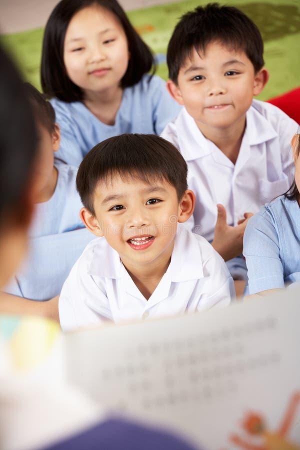 Leraar die aan het Klaslokaal van de School van Studenten leest stock foto's