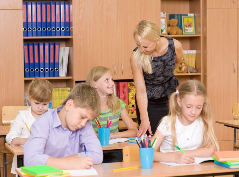 Leraar die aan studenten tijdens examen spreken stock foto's