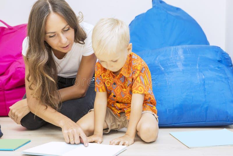 Leraar die de aandacht van de jongen vestigt met tekeningen stock afbeeldingen