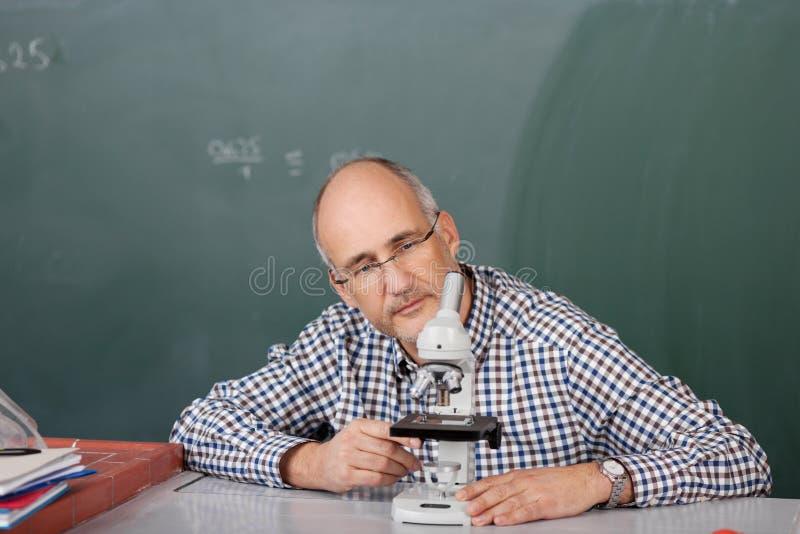 Leraar die een microscoop bekijken stock foto