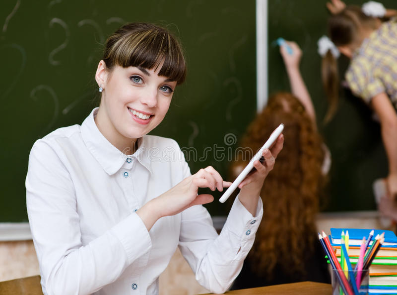 Leraar die een tabletcomputer houden bij klaslokaal het bekijken camer royalty-vrije stock fotografie